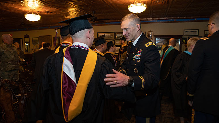 Military officer talking to student at defense and strategic studies commencement ceremony.